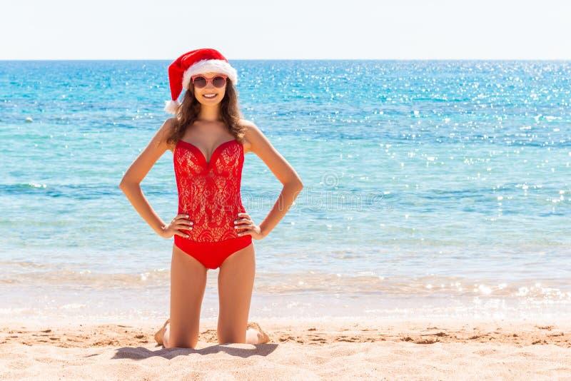 Maillot de bain de femme sexy et chapeau de port de Noël sur la plage Vacances d'hiver Copiez l'espace images libres de droits