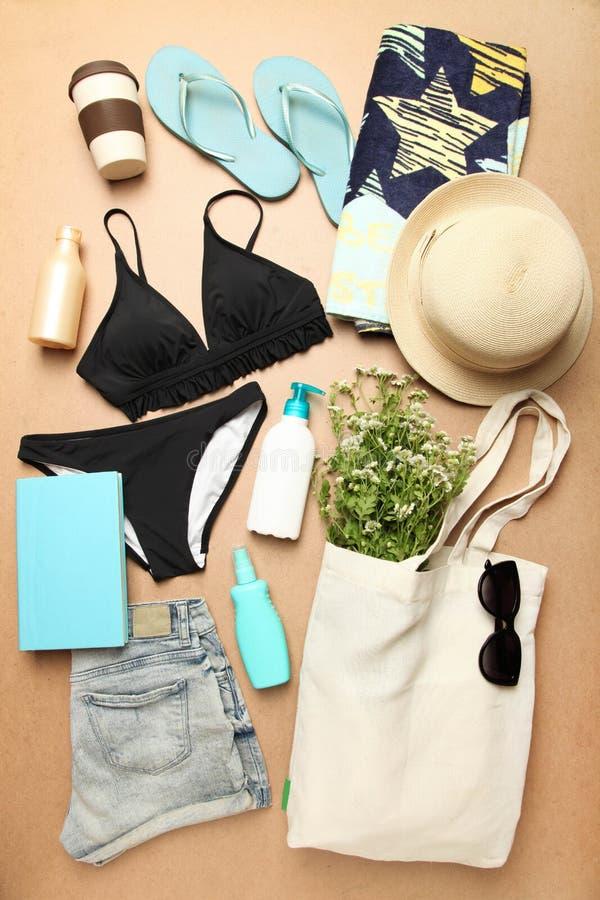 Maillot de bain noir femelle, chapeau de paille, serviette de plage images stock