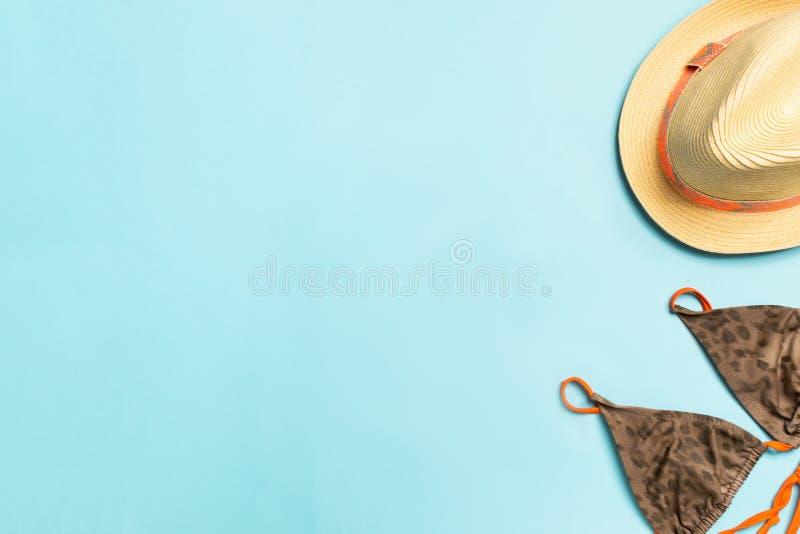 Maillot de bain de pailles de chapeau d'accessoires de plage d'été sur un fond bleu Le concept des loisirs et de la plage Copiez  image stock