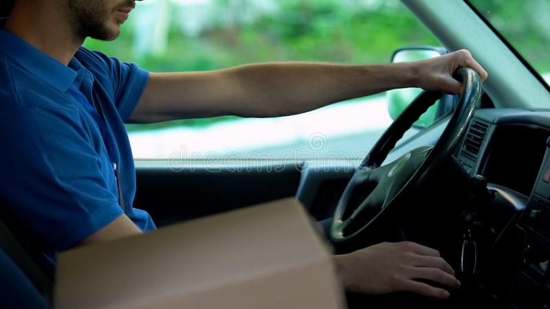 Mailman driving car, cardboard box standing near him, parcels express delivery stock images