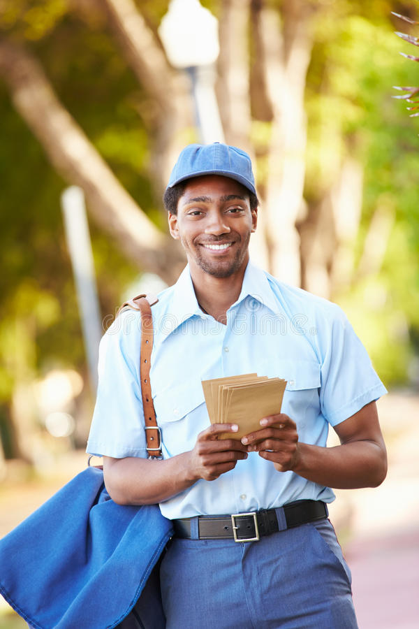 Mailman Walking Along Street Delivering Letters stock photography