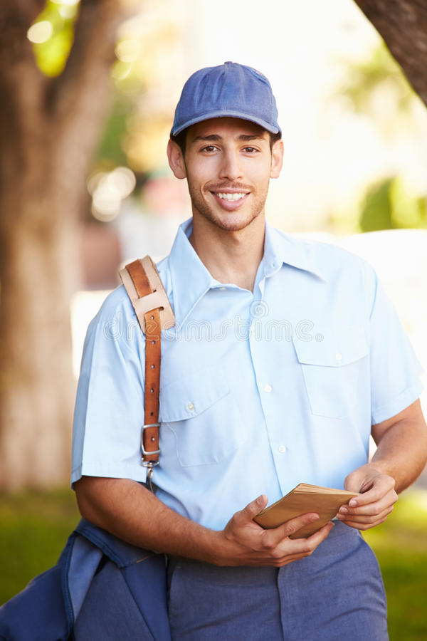 Mailman Walking Along Street Delivering Letters royalty free stock images