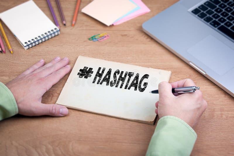 Main écrivant Hashtag Bureau avec un ordinateur portable et une papeterie images stock