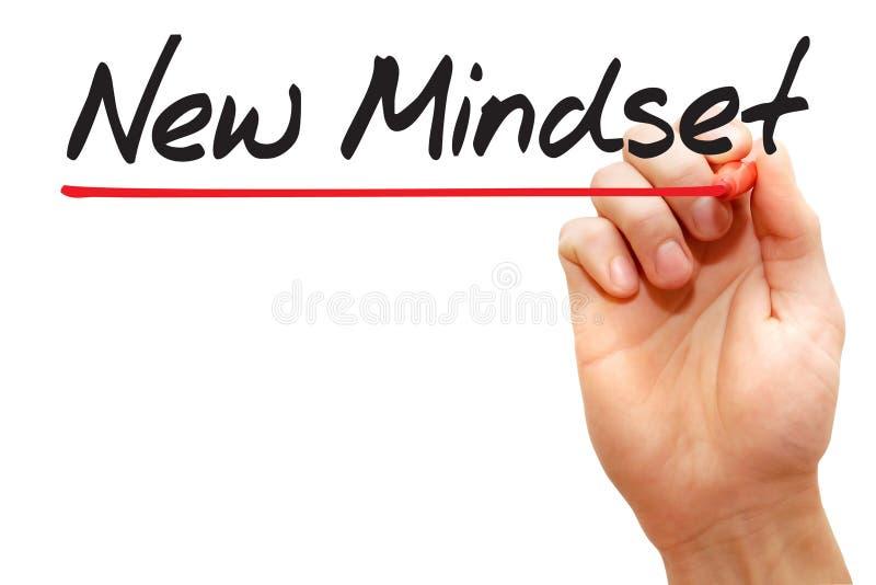 Main écrivant la nouvelle mentalité, concept d'affaires images stock