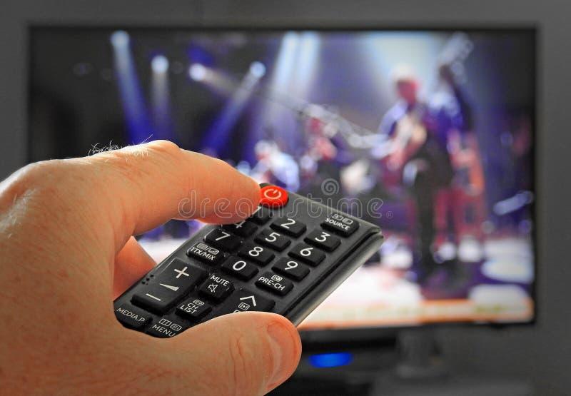 Main actionnant la TV à télécommande image libre de droits