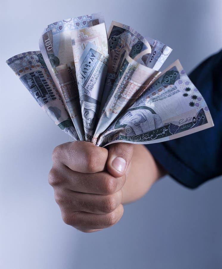Main adulte tenant un groupe de billets de banque saoudiens de riyal photographie stock