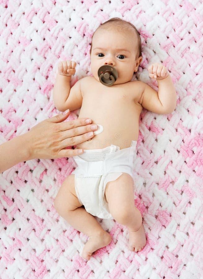 Main appliquant la lotion de corps au ventre du bébé photographie stock