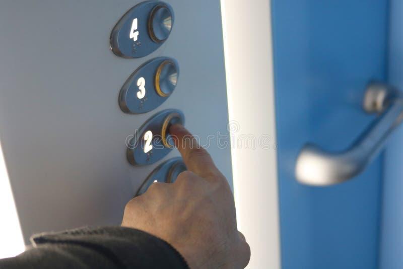 Main appuyant sur le bouton de deuxi?me ?tage dans un ascenseur image stock