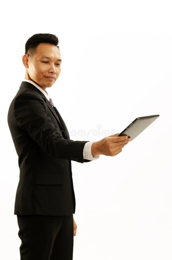 Main asiatique d'homme d'affaires tenant le comprimé et donnant vers de l'isolant image stock