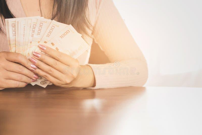 Main asiatique de femme d'affaires tenant l'argent surfaçant pour investir ou le paiement photos libres de droits