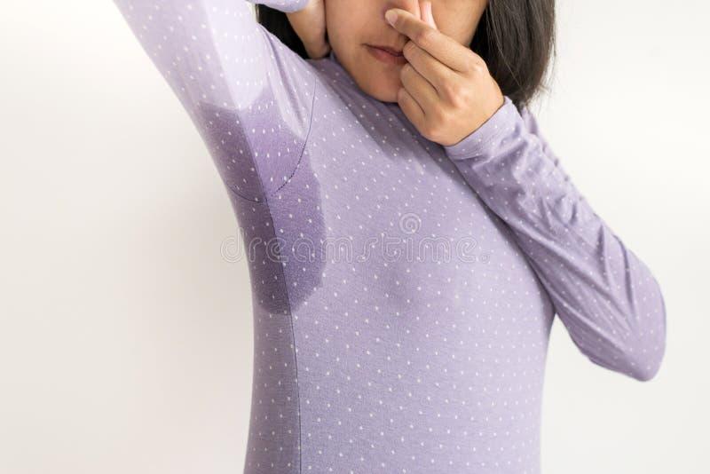 Main asiatique de femme serrant le nez avec la transpiration d'odeur, femelle sentant ou reniflant son aisselle, mauvaise odeur photographie stock