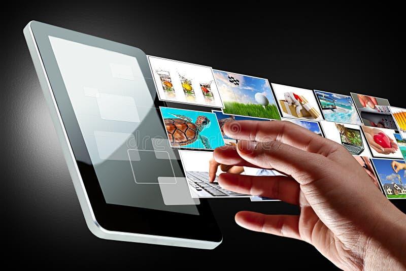 Main atteignant coulant des multimédia de la tablette images stock