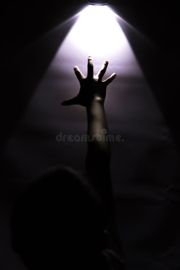 Main atteignant jusqu'au contact une lumière rougeoyante images libres de droits