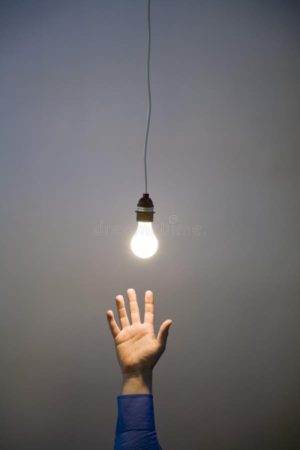 Main atteignant pour l'ampoule photos stock