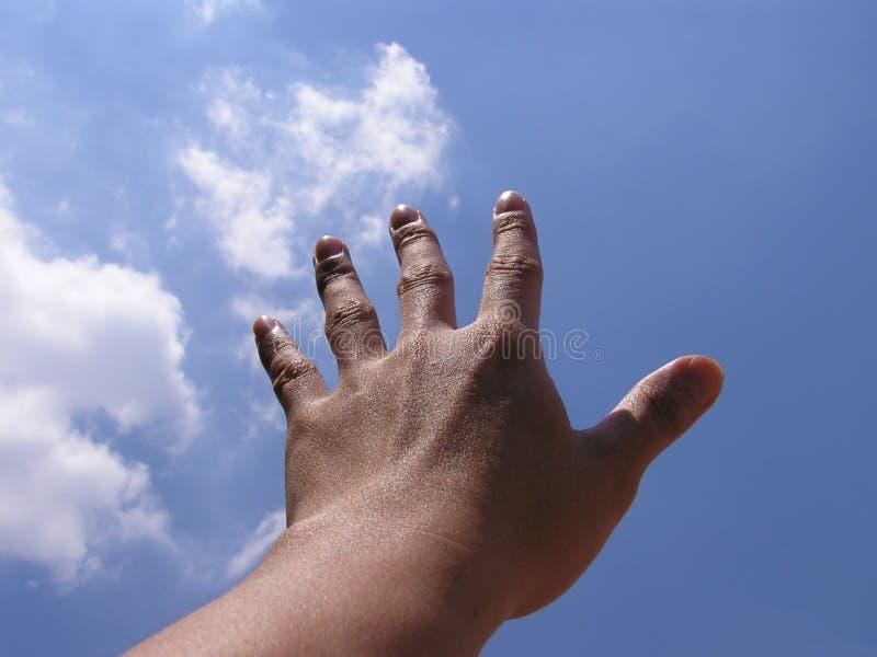 Main atteignant pour le ciel photo libre de droits