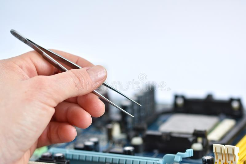 Main au-dessus de conseil avec des composants Réparation des ordinateurs et des technologies modernes photo stock