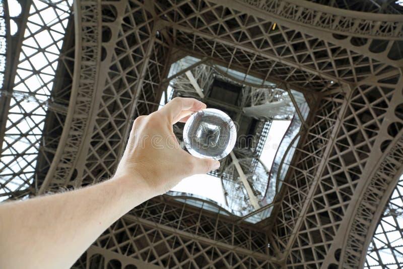 main avec de la boule de cristal sous Tour Eiffel à Paris en franc images stock
