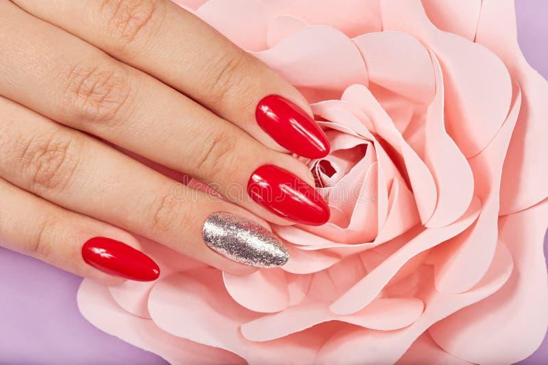 Main avec de longs beaux ongles manucurés rouges artificiels et fleur rose rose photo libre de droits