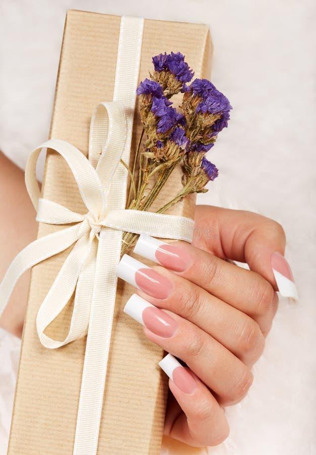 Main avec de longs ongles manucurés français artificiels tenant un boîte-cadeau avec l'arc photographie stock libre de droits