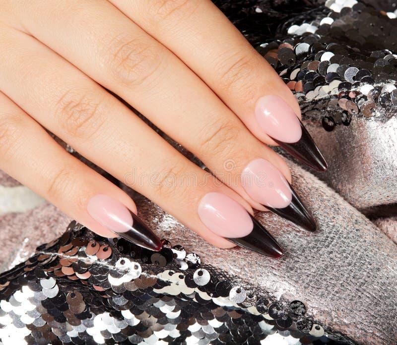Main avec de longs ongles manucurés français noirs artificiels images stock