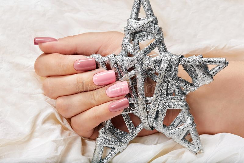 Main avec de longs ongles manucurés roses artificiels tenant un jouet argenté de Noël d'étoile photographie stock