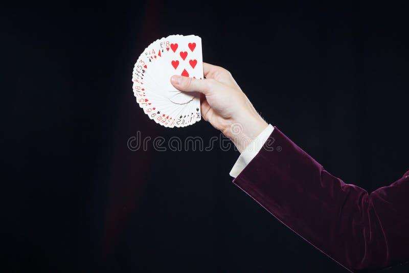 Main avec des cartes en gros plan La section médiane de l'apparence de magicien a éventé des cartes sur le fond noir Magicien, jo photo libre de droits