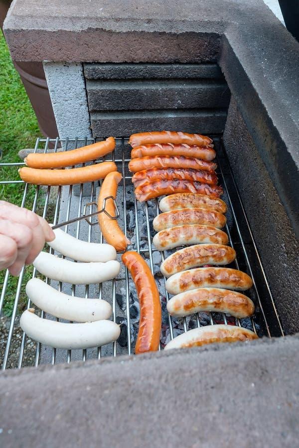 Main avec des pinces et des saucisses de barbecue au-dessus d'un gril photo stock