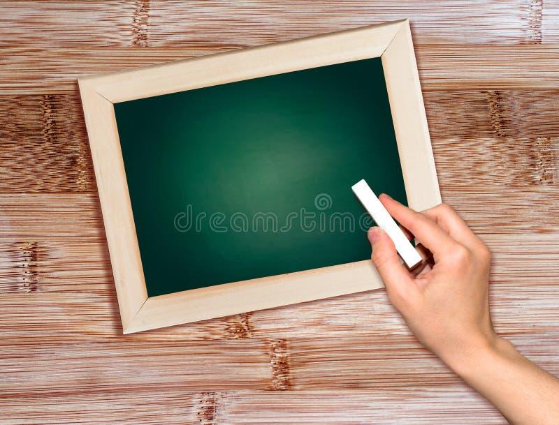 Main avec l'écriture de craie sur le tableau noir. photo libre de droits