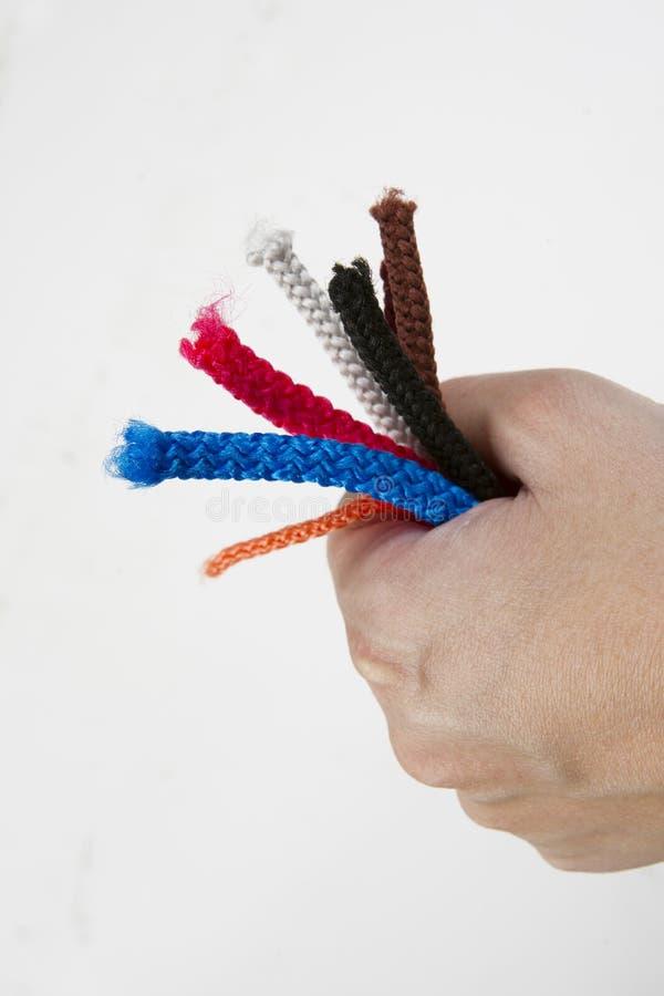 Main avec l'extrémité colorée de la corde photographie stock