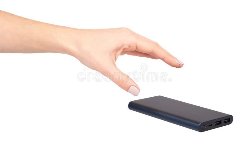 Main avec la banque bleu-foncé de puissance pour les périphériques mobiles de remplissage, batterie externe photographie stock libre de droits