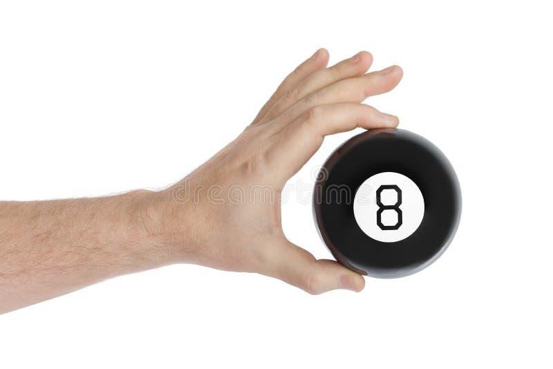 Main avec la boule de billard magique numéro huit images stock