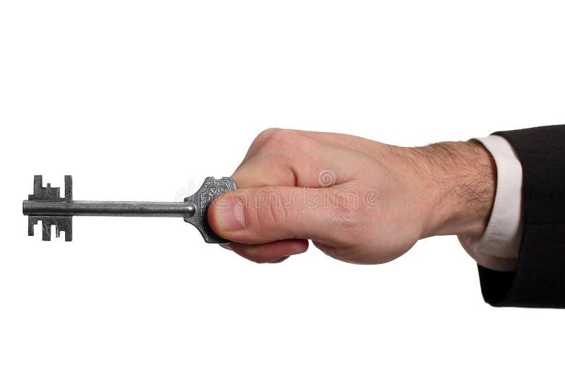 Main avec la clé d'isolement sur le fond blanc image stock