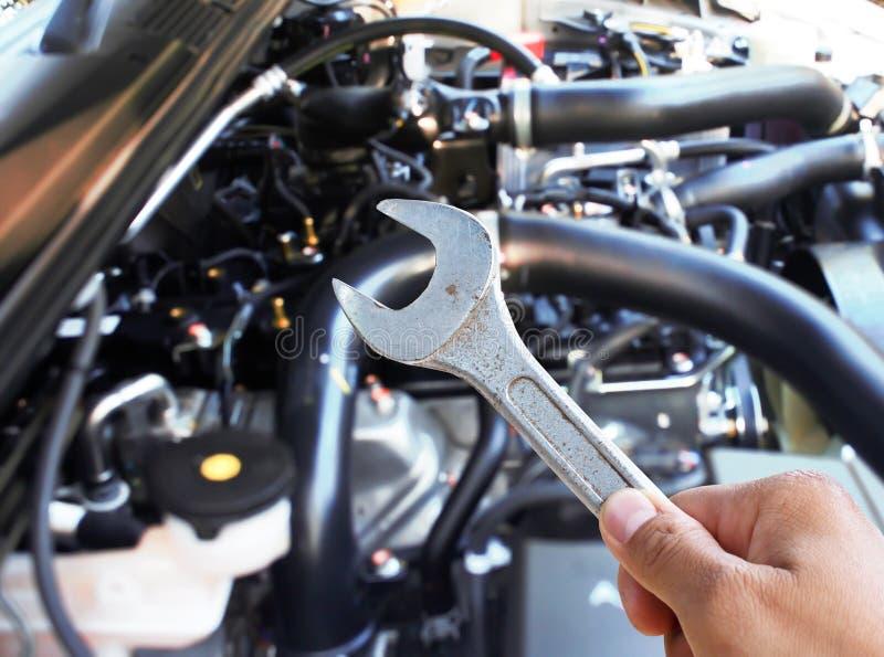 Main avec la clé vérifiant le moteur de voiture images libres de droits