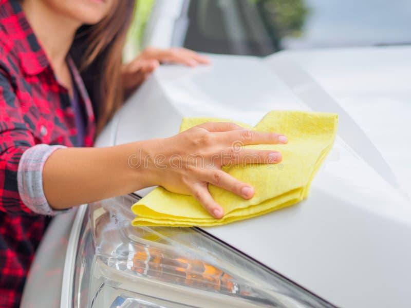 Main avec la voiture blanche de nettoyage de tissu jaune de microfiber image libre de droits