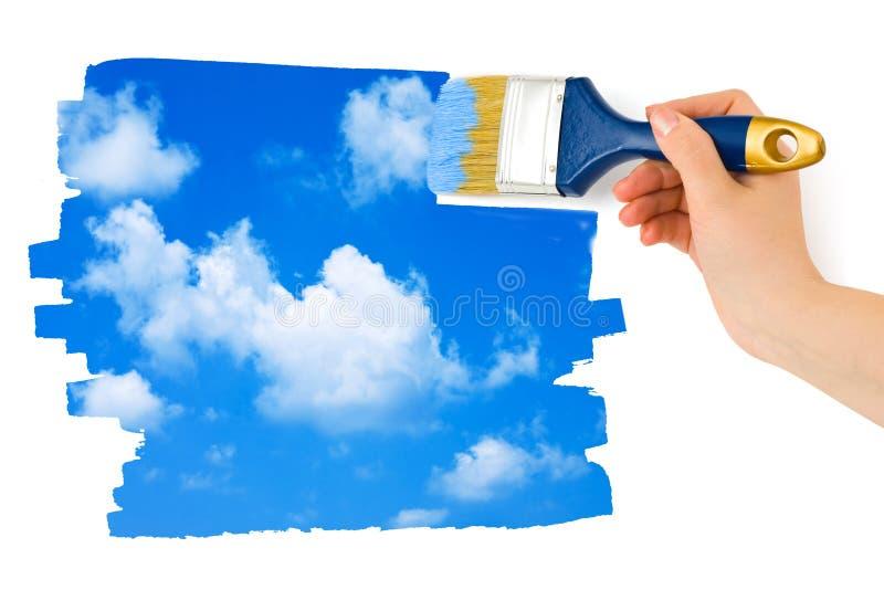 Main avec le ciel de peinture de pinceau photographie stock