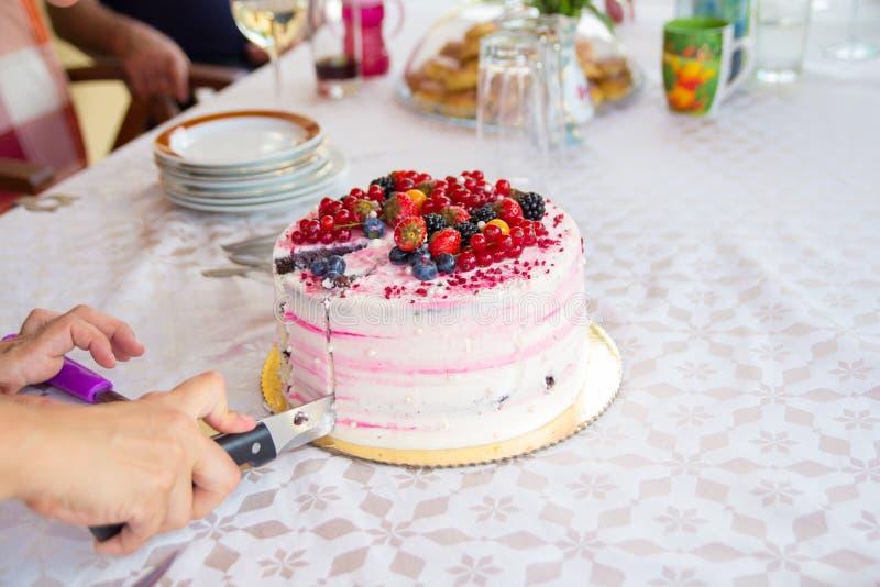 Main avec le couteau découpant le gâteau d'anniversaire en tranches images libres de droits