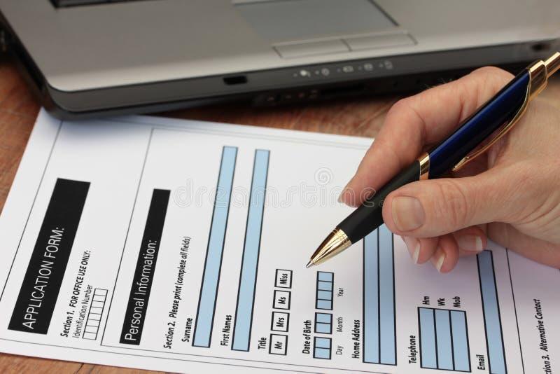 Main avec le crayon lecteur remplissant le formulaire factice avec Lapt photographie stock libre de droits