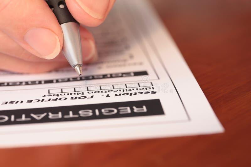 Main avec le crayon lecteur remplissant le formulaire sur le plan rapproché de Tableau image stock