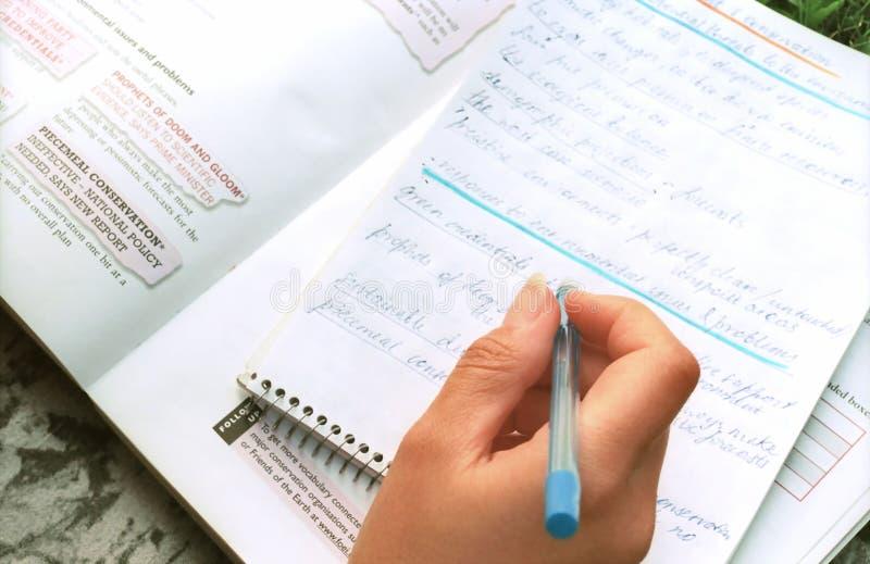 Main avec le crayon lecteur sur le livre d'exercice images libres de droits