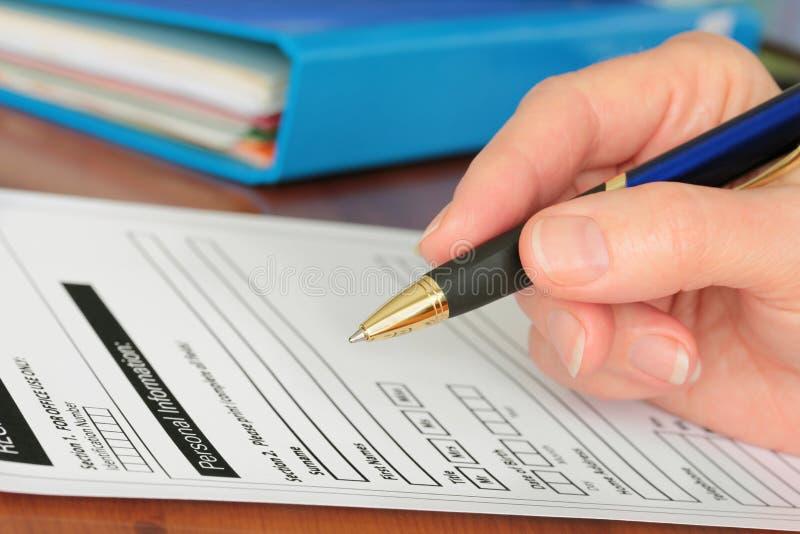 Main avec le crayon lecteur terminant l'information personnelle sur la forme image libre de droits