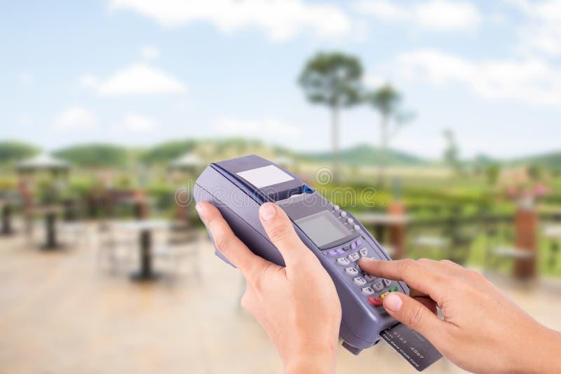 Main avec le grand coup de carte de crédit par le terminal à vendre images libres de droits