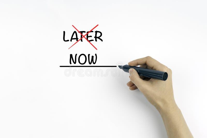 Main avec le marqueur écrivant le texte - plus tard ou maintenant images stock