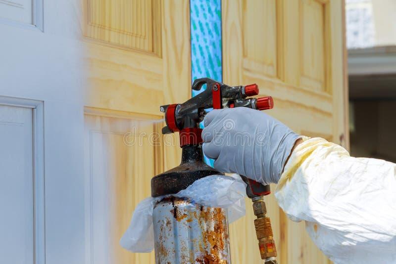 Main avec le pistolet de pulvérisation peignant la porte en bois images libres de droits