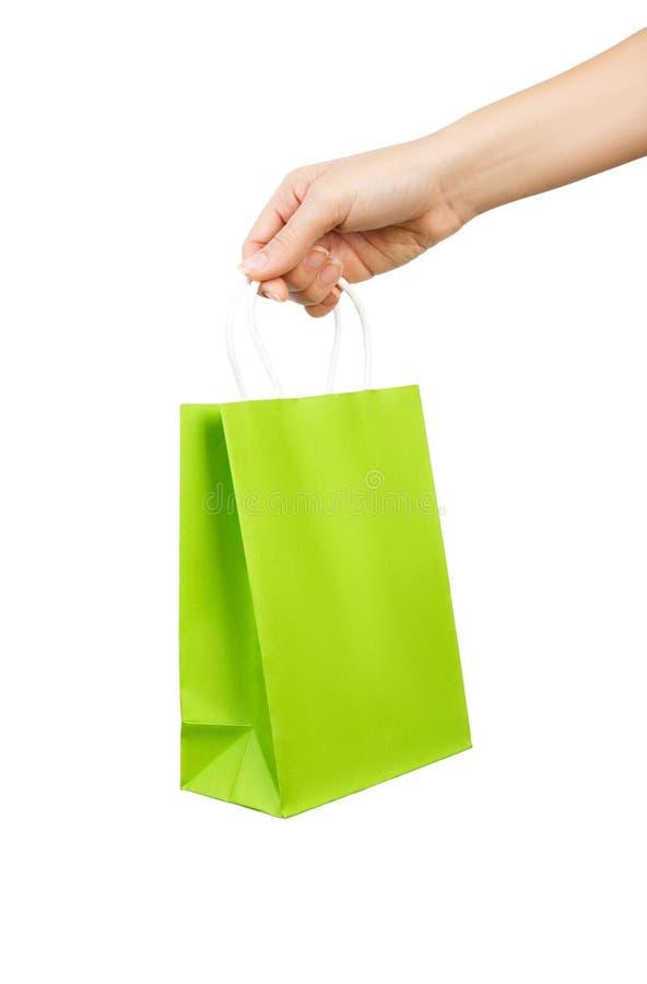 Main avec le sac vert d'isolement sur le fond blanc photo stock