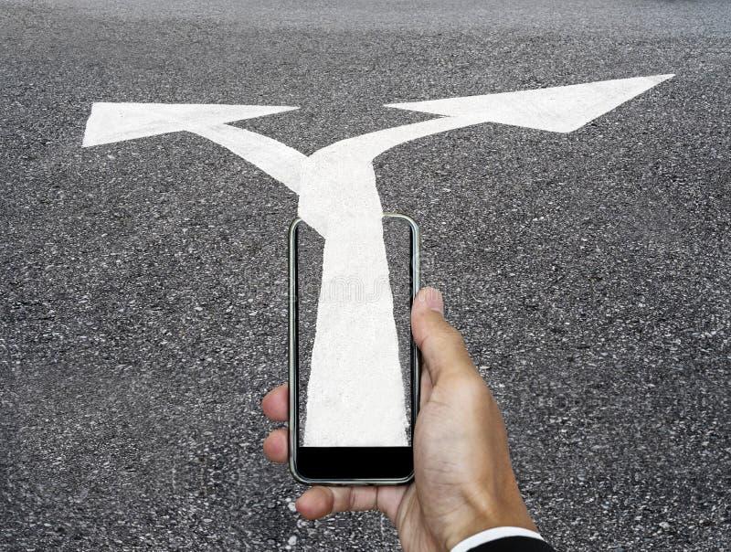 Main avec le téléphone intelligent et directions bi-directionnelles de flèche de téléphone à la route, concept d'affaires image stock