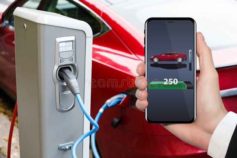 Main avec le téléphone sur un fond de point de remplissage de voiture électrique photos libres de droits