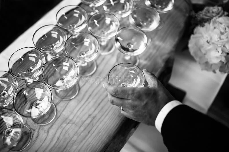 Main avec le verre à vin Beaucoup de verres à vin sur une table en bois photographie stock libre de droits