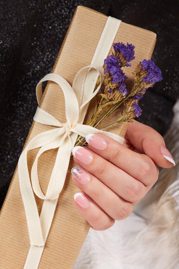 Main avec les ongles manucurés français artificiels tenant un boîte-cadeau photographie stock libre de droits