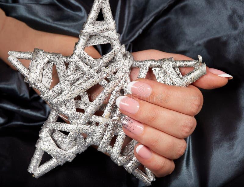 Main avec les ongles manucurés français artificiels tenant une étoile argentée photo stock