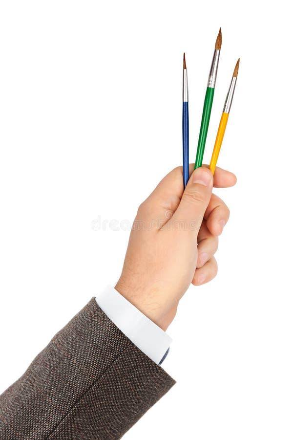 Main avec les pinceaux multicolores photographie stock libre de droits